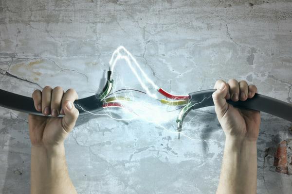 mani che tengono cavi elettrici