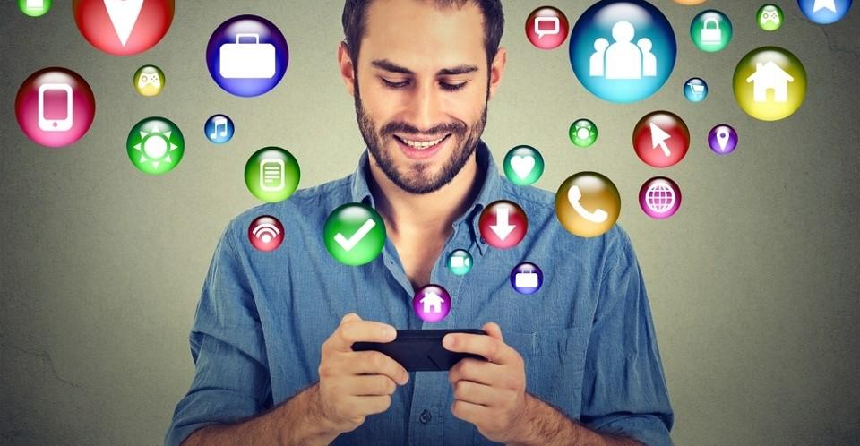 uomo con smartphone da cui escono immagini simboliche di app